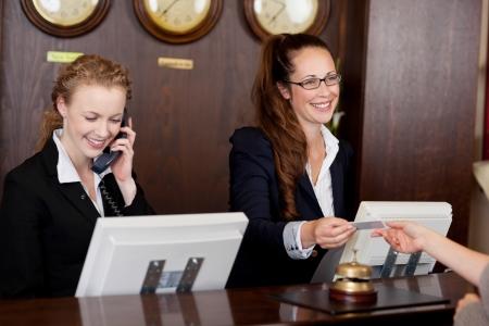 Dos hermosas recepcionistas elegantes jóvenes en un área de recepción, uno que habla en el teléfono y el otro que da una tarjeta a un cliente Foto de archivo