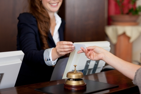 front desk: smiling female receptionist passing card to guest Stock Photo