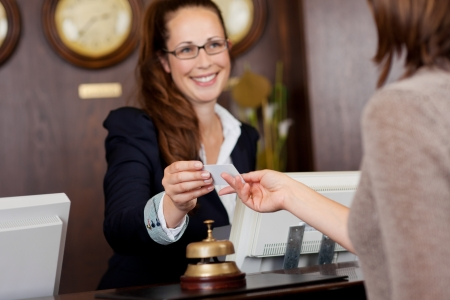 温かみのある歓迎笑顔、顧客にビジネス カードを引き渡す美しい受付係 写真素材