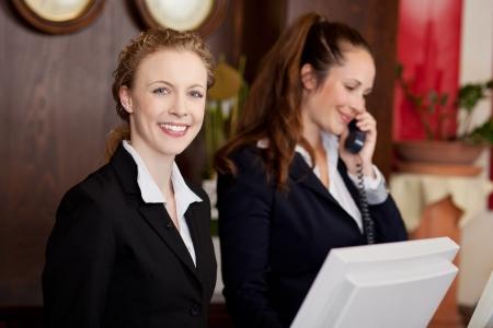 recep��o: Duas mulheres atrativas novas trabalhar como recepcionistas profissionais em um hotel
