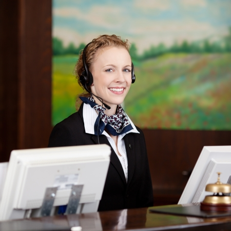 Friendly female receptionist wearing a headset at the reception of the hotel Stock Photo - 21375239