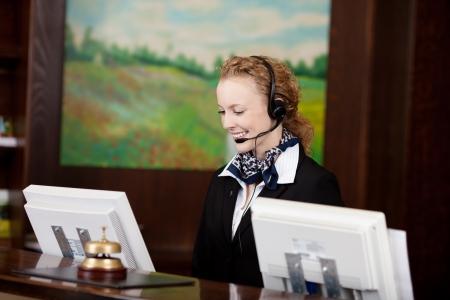 Réceptionniste souriante portant un casque de travail derrière un comptoir de réception sur son ordinateur, comme elle prend un appel d'un client