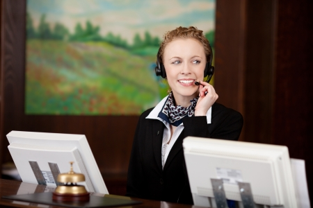 Young woman using headset while working at the reception of a hotel Stock Photo - 21375240