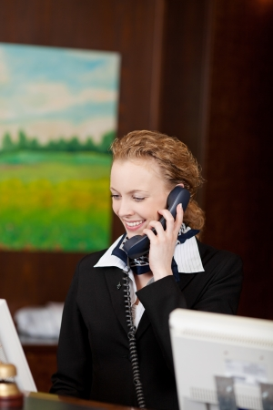 Young female receptionist smiling while answering the telephone at the reception desk of a hotel Stock Photo - 21375250