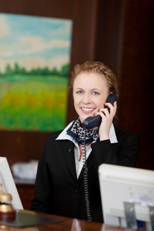 Jonge aantrekkelijke vrouwelijke receptioniste beantwoorden van de telefoon in een hotel