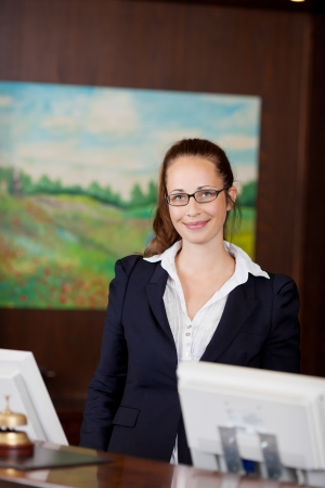 Smiling receptionist wearing glasses standing behind the reception desk at a hotel in front of her computer photo