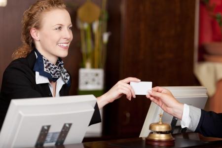 フロント デスクでは、クライアントに空白の白いカードを引き渡すスタイリッシュな美しい受付係の笑みを浮かべてください。