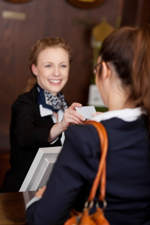 costumer: Guest receiving a business card at reception from a beautiful smiling young receptionist with focus to the card