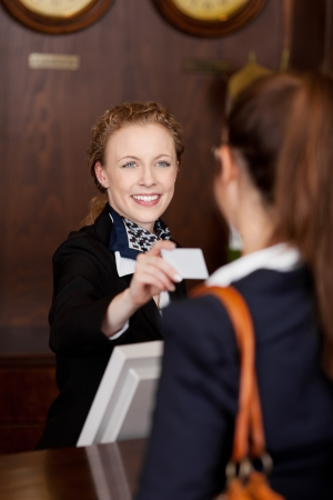 front desk: Smiling stylish young receptionist handing out a business card to a customer in a hotel lobby