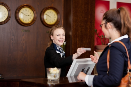 Guest at an international hotel requesting a business card at reception from the beautiful stylish receptionist