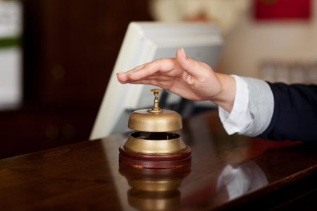 reception desk: Close-up of a hand ready to press the bell at the reception of a hotel