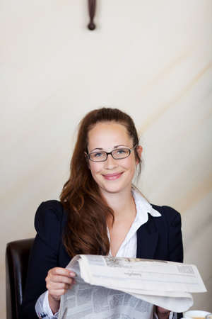 Friendly businesswoman with a beautiful smile wearing glasses reading a newspaper in a hotel lobby with copyspace photo