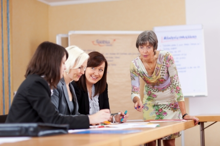 teaching adult: senior businesswoman in a meeting with colleagues