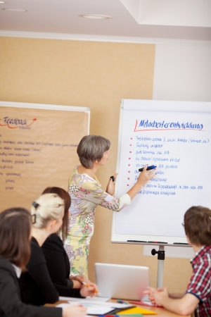 Woman giving a presentation on a flipchart to a group of young business students photo