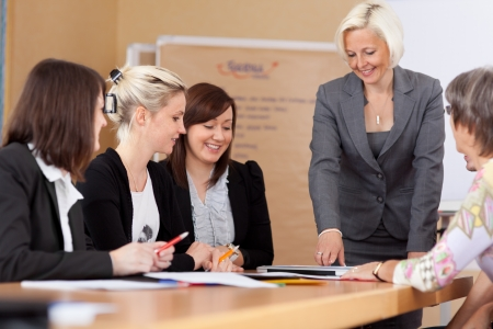 Women in a business meeting seated around a table listening to their leader or manager giving a report