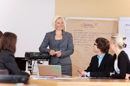 Lachend zakenvrouw geeft een presentatie aan een groep zakenmannen en-vrouwen zittend aan een tafel