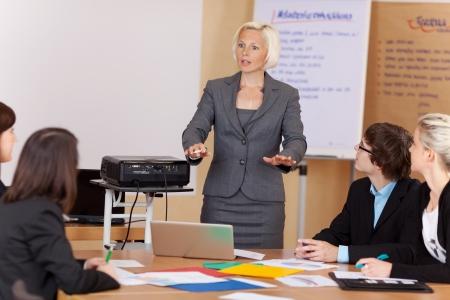 Vrouw zongen een projector die een corporate training klasse om een groep van jonge ondernemers rond een tafel gebaren met haar handen als ze iets uitlegt Stockfoto
