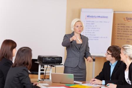 Mujer madura atractiva que da una presentación de negocios a un grupo diverso de personas sentadas alrededor de una mesa Foto de archivo