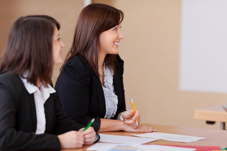Two women in a business meeting with focus to one attractive smiling lady looking topwards a flipchart photo