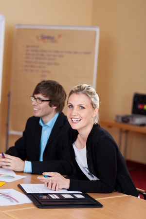 turning table: Attractive businesswoman in a meeting sitting at a table with her colleagues turning to smile at the camera