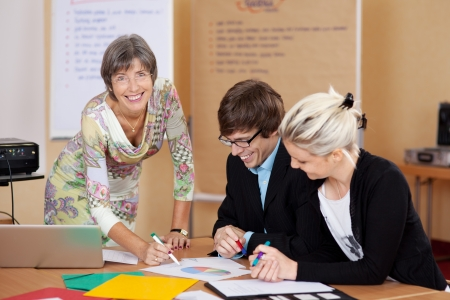 Happy female manager supervising the work of the young employees, in the office Stock Photo - 21375378