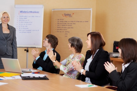 Business class applauding the female lecturer at the end of a training class or presentation photo