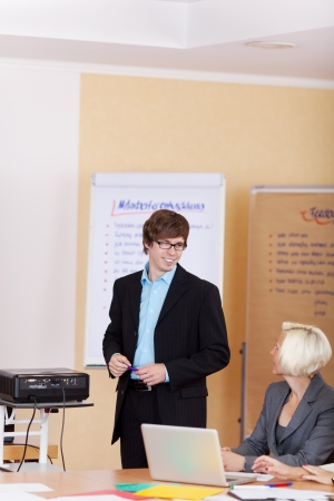 Confident young male employee making a business presentation with video projector and paperboard photo