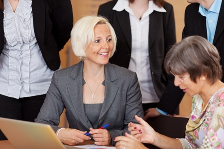 Two middle-aged business women discussing a project surrounded by other employees photo