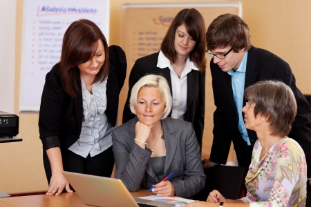 Business team of diverse young people gathered around a laptop looking at the screen with serious expressions photo