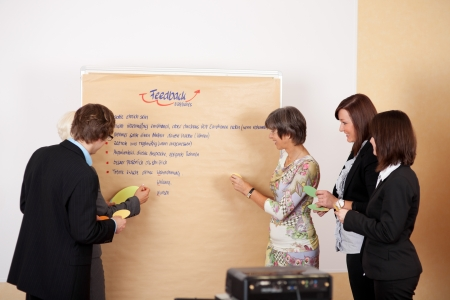 United business team having a brainstorming and writing ideas on a paperboard photo