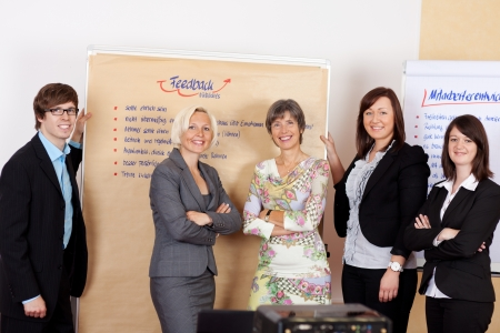Confident happy business team standing in front of two paperboards, after brainstorming in the office photo