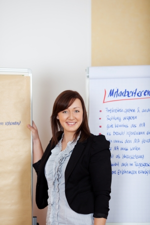 Confident cheerful professional female employee standing in front of the paperboards in the office photo
