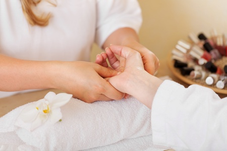 handcare: Beautician giving a manicure in a spa or wellness centre , close up view of the hands