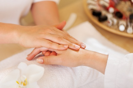handcare: female therapist giving a hand massage to woman