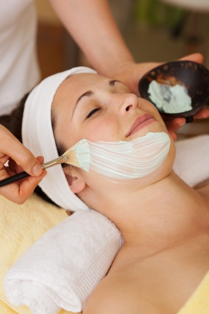 spat: Beautician applying a face mask during a skincare treatment to a beautiful young woman in a spa