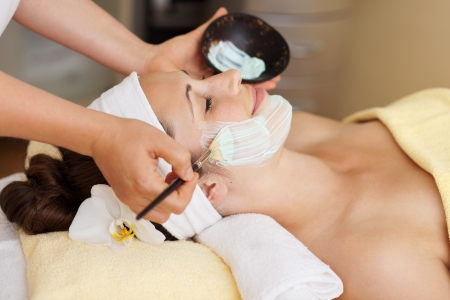 Therapist applying a face mask to a beautiful young woman in a spa using a cosmetics brush