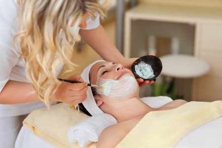 hydrate: Beautician applying a face mask to a beautiful smiling woman with a cosmetics brush in a wellness centre or spa Stock Photo