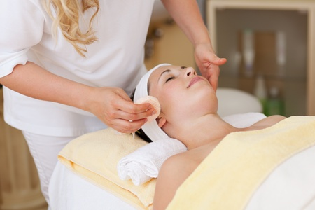 wellness center: Woman laying on a massage table while receiving a hydrating facial treatment, at a wellness center