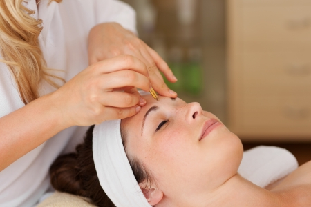 aesthetic: Young woman being pampered in a spa lying with her eyes closed in contentment as the therapist gives her a facial massage Stock Photo