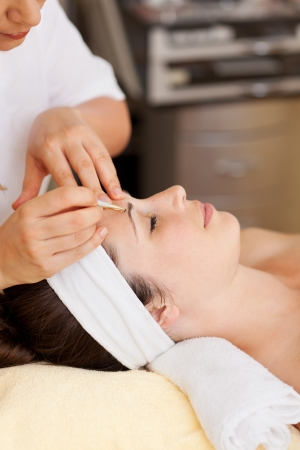 tweezers: Beautician plucking a beautiful young womans eyebrows with tweezers in a beauty salon