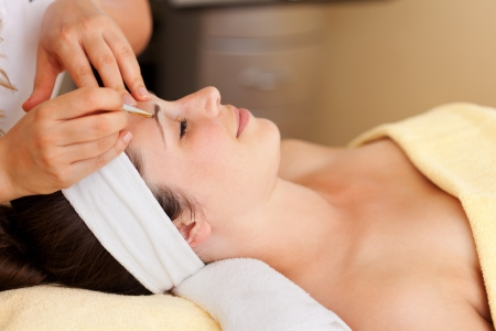tweezing: Beautiful woman having her eyebrows plucked by a beautician in a spa or beauty salon in a wellness concept Stock Photo