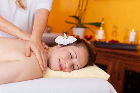 dayspa: Woman with a beautiful smile on her face and a serene expresson having a relaxing massage in a spa
