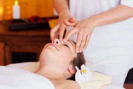 head massage: Woman having a facial massage in a spa with the therapist using her fingertips to exert pressure on the forehead for relaxation