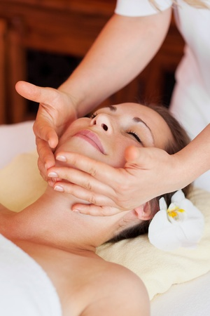 massage therapy: Young beautiful woman receiving a relaxing facial massage at a spa center