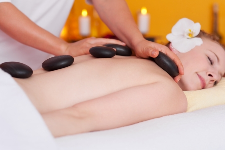 Young woman lying on a massage table with hot stones on her back in a wellness center photo