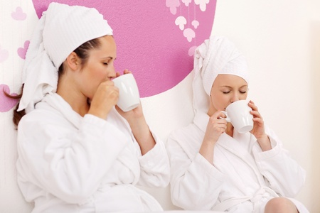 bath robes: Two beautiful young women with towels on her heads wearing spa bath robes and enjoying a cup of tea