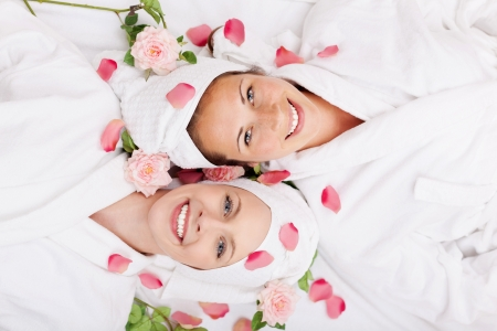 2 persons: Two happy friends in a wellness centre lying head to head on their backs smiling up at the camera covered in rose petals Stock Photo