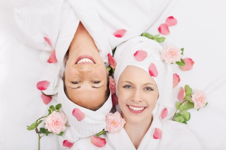 Two smiling friends in a spa lying head to head on their backs smiling up at the camera covered in rose petals and fresh roses