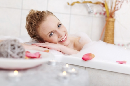 Beautiful woman relaxing in a foamy bubble bath resting her head on the side and smiling at the camera in appreciation and enjoyment photo