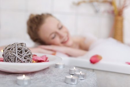 lying in bathtub: Beautiful woman soaking in a bubble bath with her eyes closed in bliss with focus to the candles in the foreground